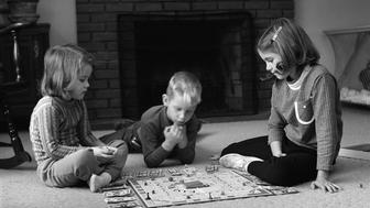 Two girls and boy (4-5, 6-7) playing Monopoly in front of fireplace