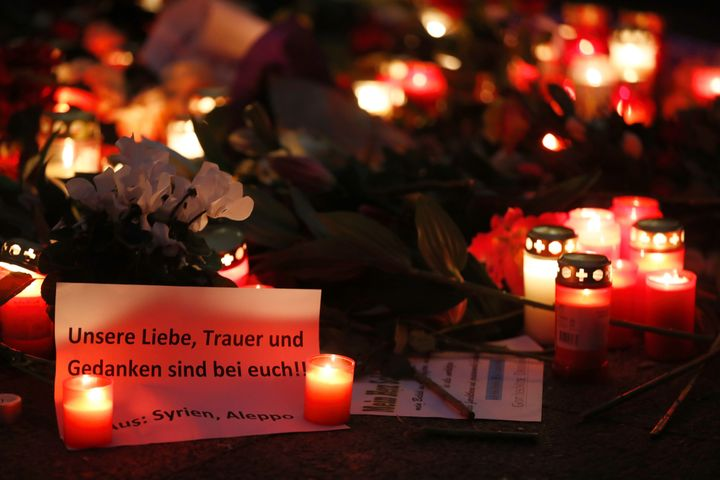 """A paper reading """"Our love, mourning and thoughts are with you"""" lies between candles on Dec. at a makeshift memorial for the v"""