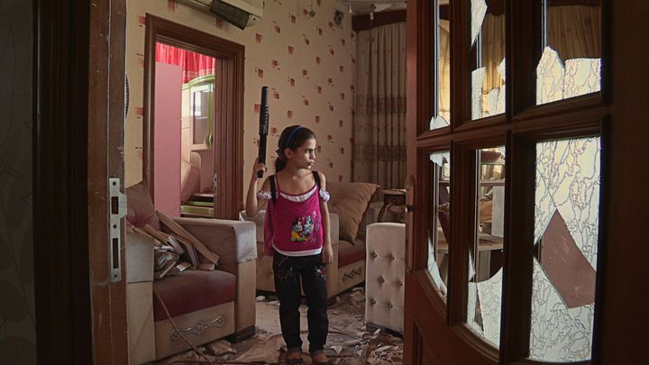 Farah emulates her father with a toy gun in their old Aleppo apartment.