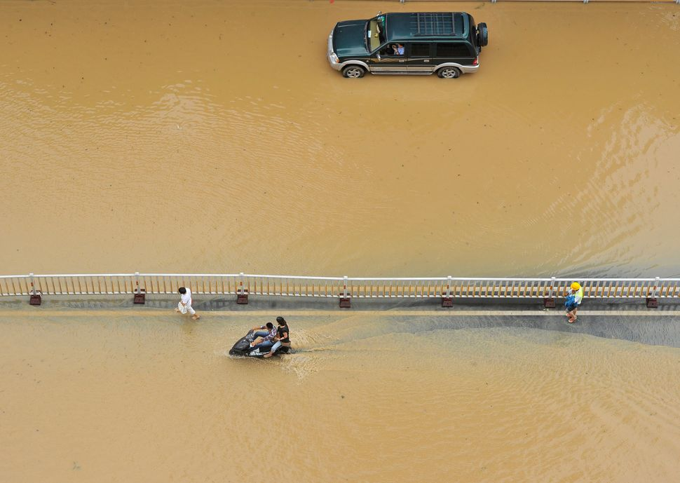 A vehicle and a motorcycle make their way through a flooded road after Typhoon Meranti hit on Sept. 15 in Fuzhou, Fujian Prov