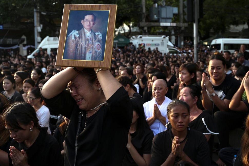 A woman cries while holding up a portrait of Thailand's King Bhumibol Adulyadej while his body is being moved from the Bangko