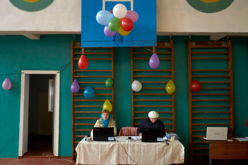 Polling staff wait to register voters at a polling station on Nov. 13 in Calfa, Moldova. Moldovans cast their votes in a pres