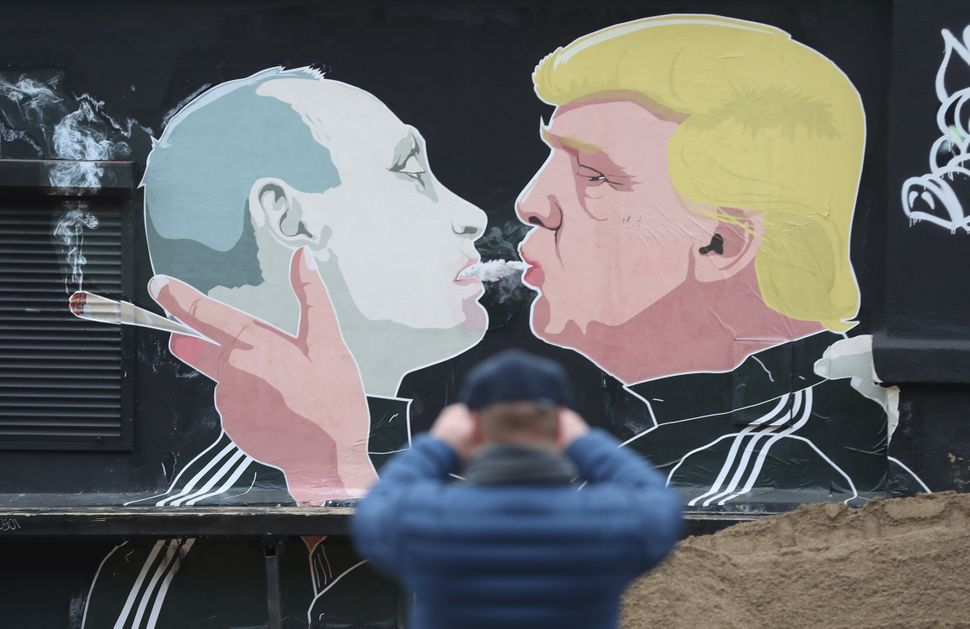 A passerby photographs a mural showing U.S. President-elect Donald Trump blowing marijuana smoke into the mouth of Russian Pr