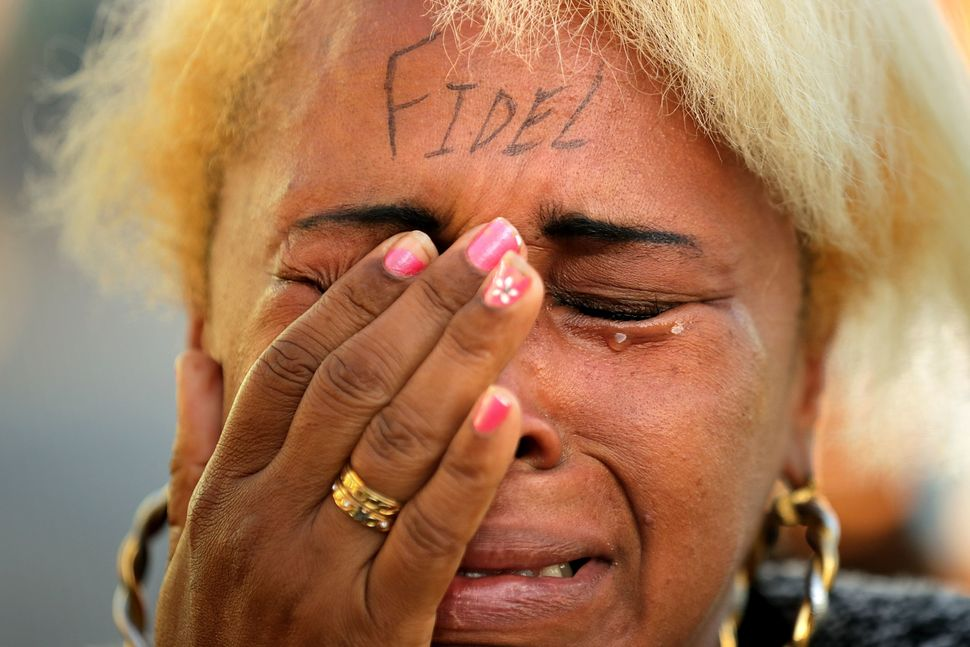 """A woman with """"Fidel"""" written on her forehead wails after joining thousands of other Cubans who lined the famous Malecó"""