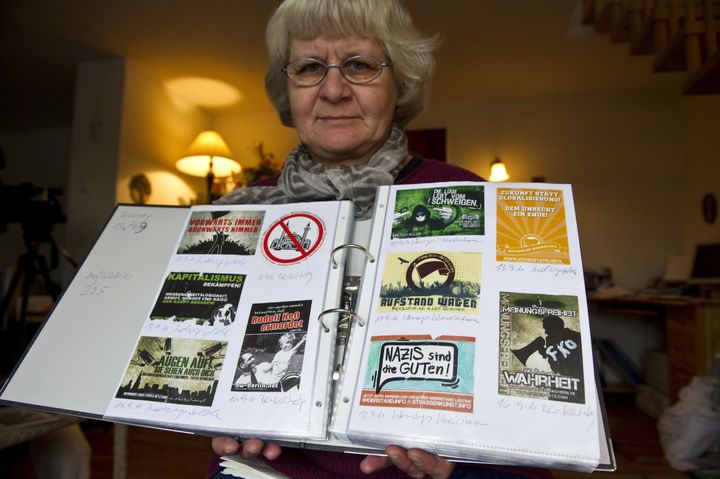 Schramm displays a scrap book containing far right and Nazi stickers she has removed from public places over the years.