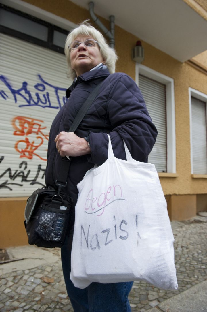 "Schramm sports a bag inscribed with the words ""Against Nazis"" when translated into English."