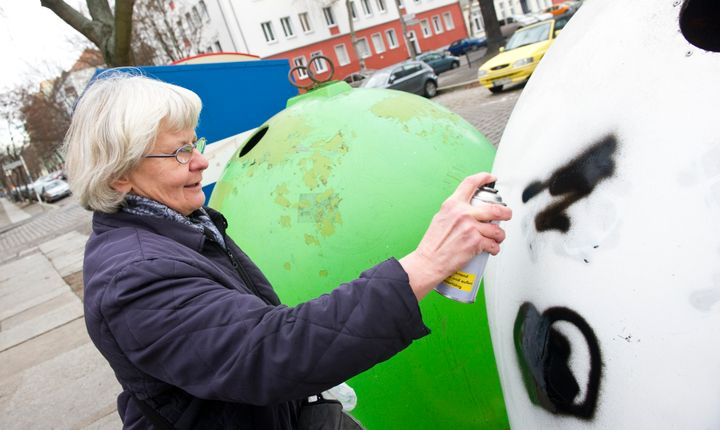 Irmela Mensah-Schramm spray paints over a Nazi symbol on a recycling bin in eastern Berlin's Lichtenberg district.