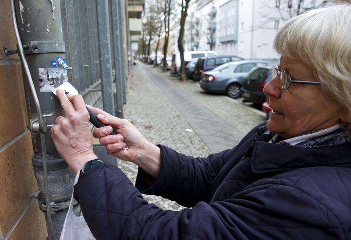 Schramm scrapes a Nazi sticker off a wall in eastern Berlin's Lichtenberg district.