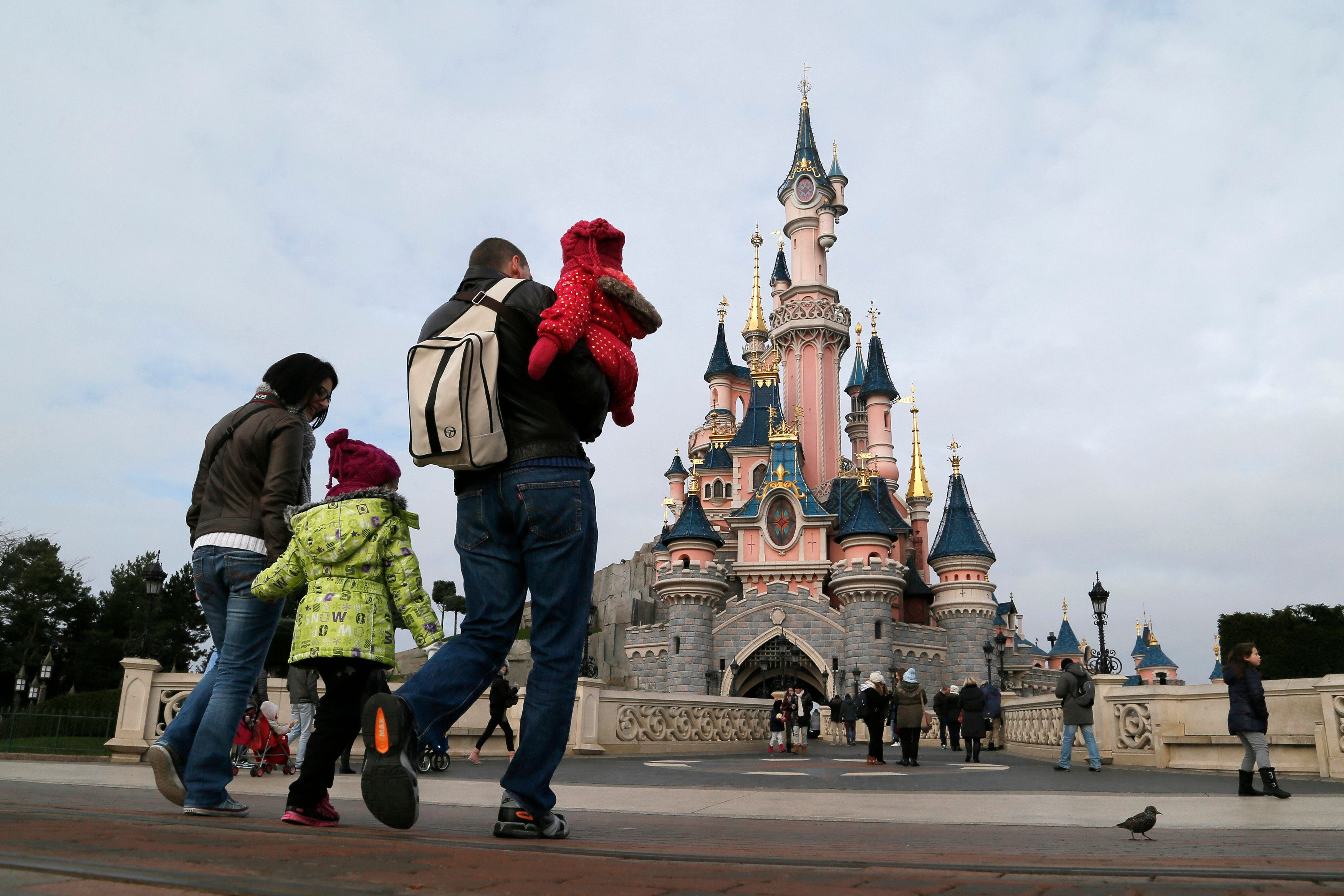 Visitors walk towards the Sleeping Beauty Castle during a visit to the Disneyland Paris Resort run by EuroDisney S.C.A in Marne-la-Vallee January 21, 2015. Picture taken January 21, 2015.  To match Special Report EURODISNEY-SHAREHOLDERS/       REUTERS/Gonzalo Fuentes (FRANCE - Tags: BUSINESS SOCIETY TRAVEL)