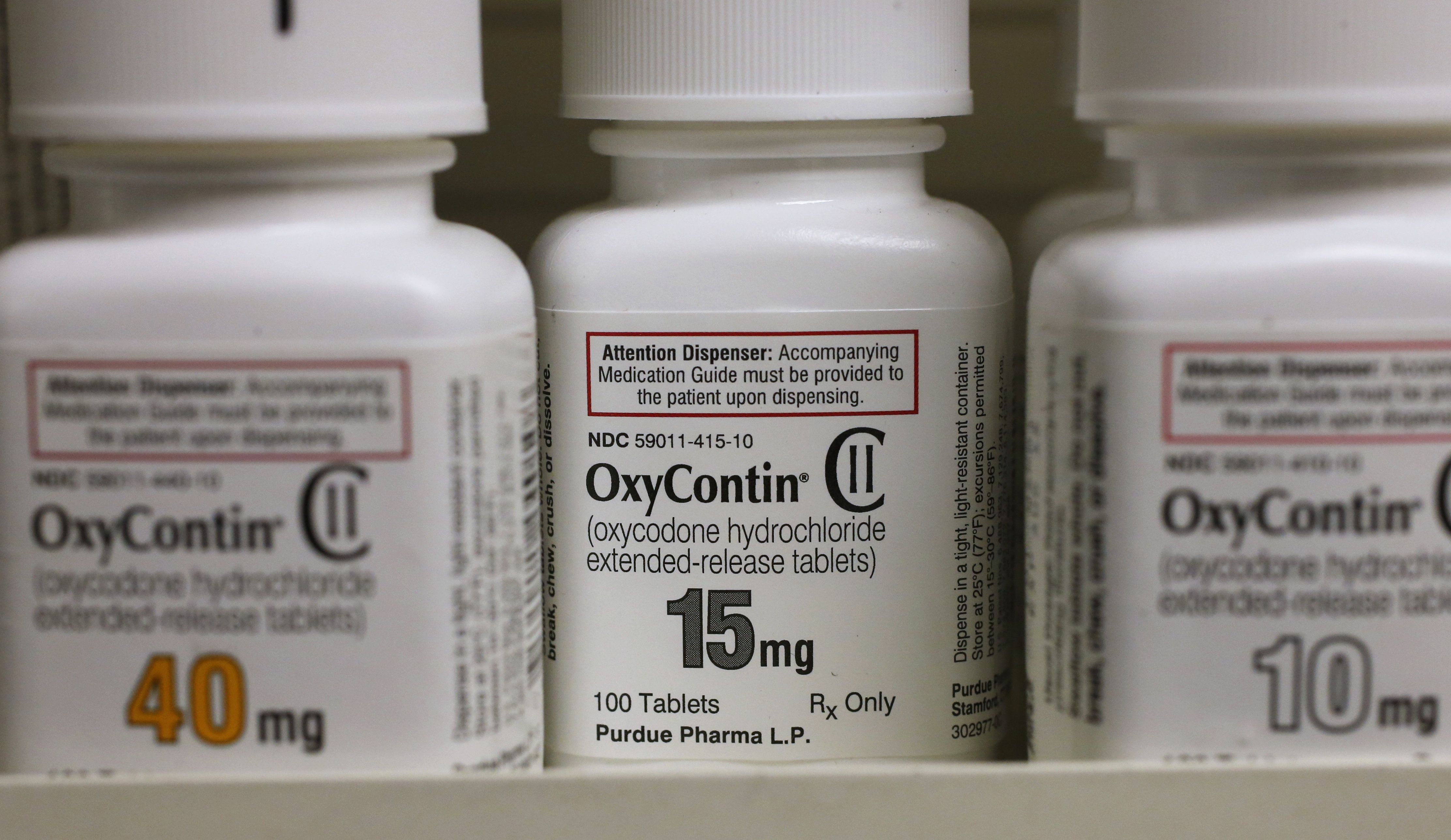 Bottles of Purdue Pharma L.P. OxyContin medication sit on a pharmacy shelf in Provo, Utah, U.S., on Wednesday, Aug. 31, 2016. A Nov. 2015 forecast from health data firm IMS Health expects global sales of brand and generic prescription drugs, and nonprescription medicines, to total $1.4 trillion in 2020. Photographer: George Frey/Bloomberg via Getty Images