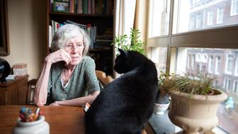 Elderly lady sitting at the table by the window on the first floor of a senior care facility, looking at her cat.