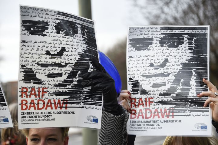 Members of Human rights NGO Amnesty International hold up portraits of jailed Saudi blogger Raif Badawi as they demonstrate i