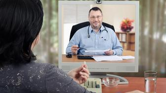 Female patient sits with her back to the camera and looks at virtual doctor in the monitor. Mature woman holds a pill by hand and ready to take it. Middle-aged bearded male doctor with glasses and a stethoscope reviews medical laboratory results with her. There are monitor, keyboard, glass water on wooden desk. Horizontal shot on blurry indoors background.