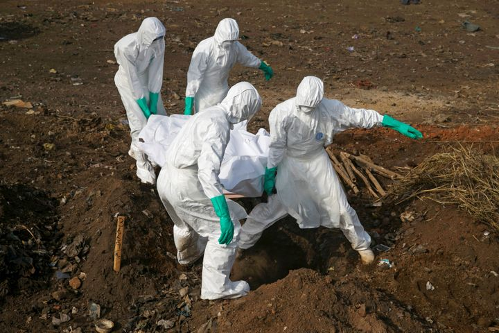 Health workers carry the body of a suspected Ebola victim for burial at a cemetery in Freetown, Sierra Leone, December 21, 2014.