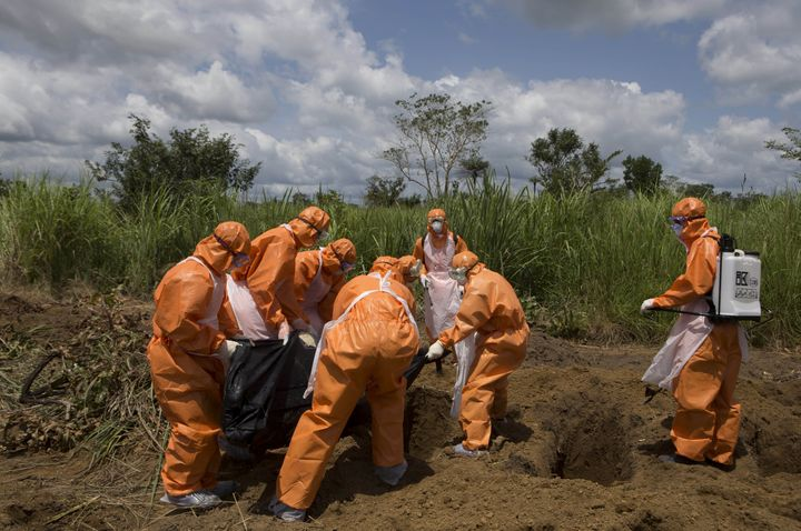 A burial team wearing protective clothes prepares an Ebola virus victim for interment, in Port Loko, Sierra Leone, September 27, 2014.