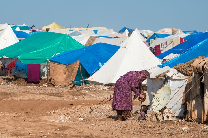 Atmeh, Syria: A Syrian woman and boy stand outside their shelter in the camp for displaced persons.