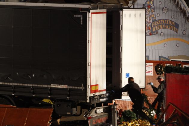 Security and rescue workers inspect a lorry truck after it was ploughed through a Christmas