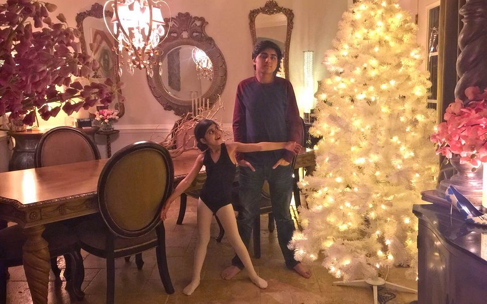 Malik's children, Eesa and Enaya, stand in front of their family Christmas tree.