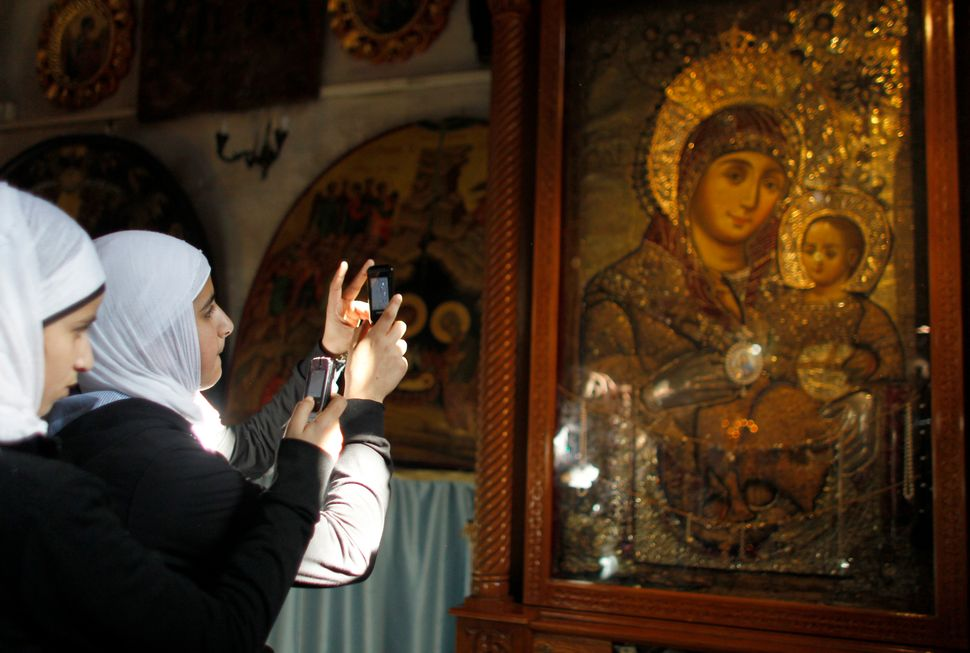 Muslim teenagers take photographs at theChurch of the Nativity, the site revered as the birthplace of Jesus, in the Wes