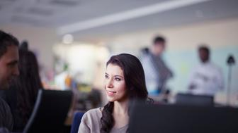 Young Hispanic adult woman talking with male man colleague eye to eye face to face chat meeting discussion conversation planning smiling pleased content satisfied interactive behind desktop laptop computer screen in busy office studio copyspace