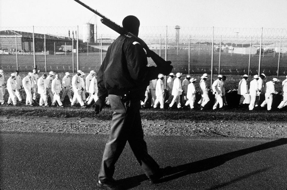 Prisoners on a chain gang are taken out for work detail by an armed guard near Harvest, Alabama in this...
