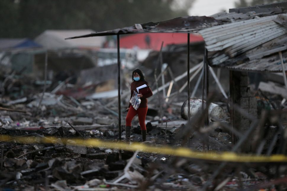 A woman walks among the remains of houses.