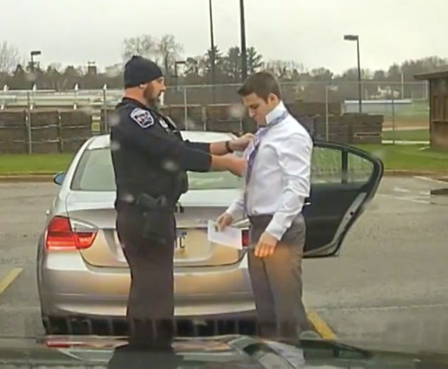 Police officer helps college student tie a necktie