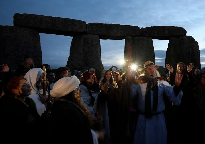 Visitors and revelers react amongst the prehistoric stones of the Stonehenge monument at dawn on Winter Solstice, the shortest day of the year, December 21, 2016.