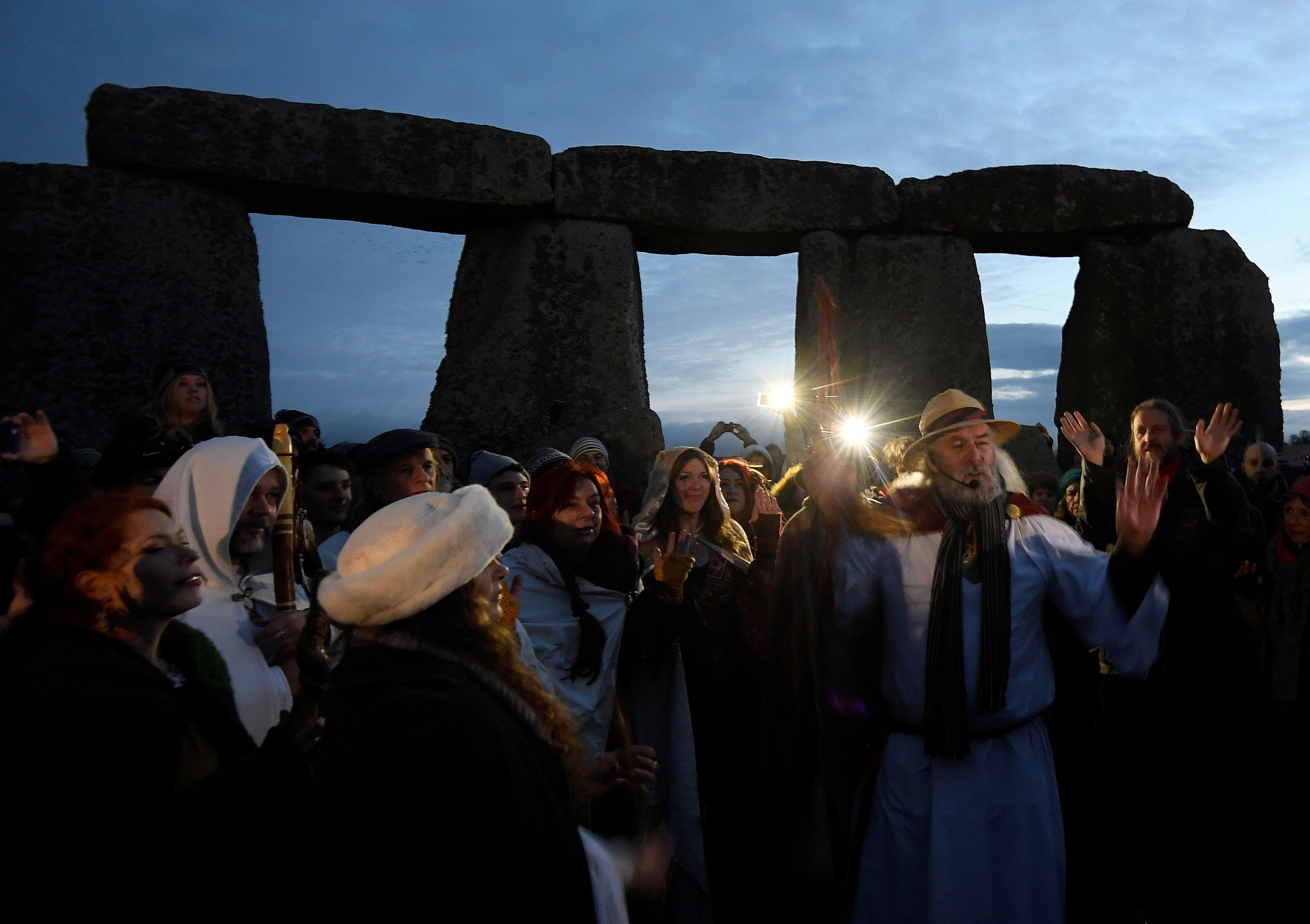 Visitors and revelers react amongst the prehistoric stones of the Stonehenge monument at dawn on Winter Solstice, the shortes