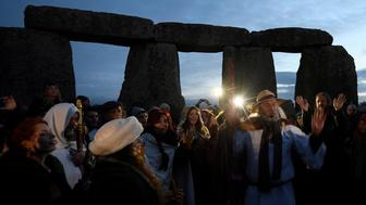 Visitors and revellers react amongst the prehistoric stones of the Stonehenge monument at dawn on Winter Solstice, the shortest day of the year, near Amesbury in south west Britain, December 21, 2016. REUTERS/Toby Melville