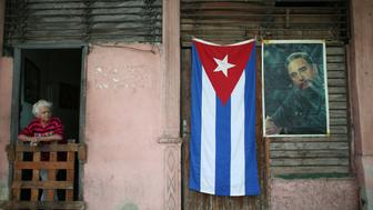 A Cuban flag and an image of Cuba's late President Fidel Castro hang on a wall as people head to Revolution Square for a massive tribute to Castro in Havana, Cuba, November 29, 2016.         REUTERS/Alexandre Meneghini