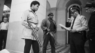 Two members of the Black Panther Party are met on the steps of the State Capitol in Sacramento, May 2, 1967, by Police Lt. Ernest Holloway, who informs them they will be allowed to keep their weapons as long as they cause no trouble and do not disturb the peace. Earlier several members had invaded the Assembly chambers and had their guns taken away.