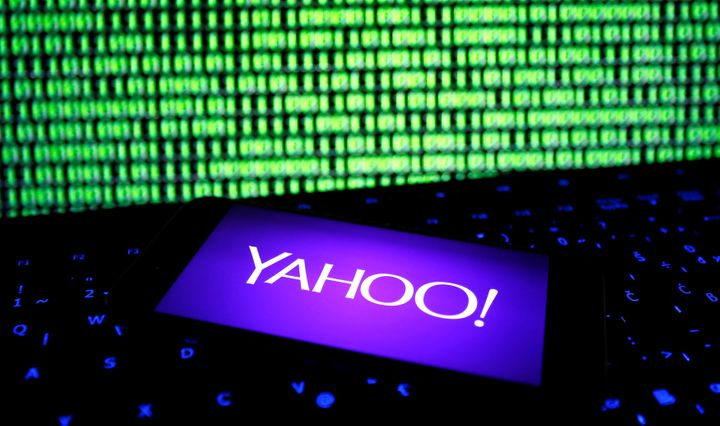 A photo illustration shows a Yahoo logo on a smartphone in front of a displayed cyber code and keyboard on December 15, 2016. (REUTERS/Dado Ruvic/Illustration)