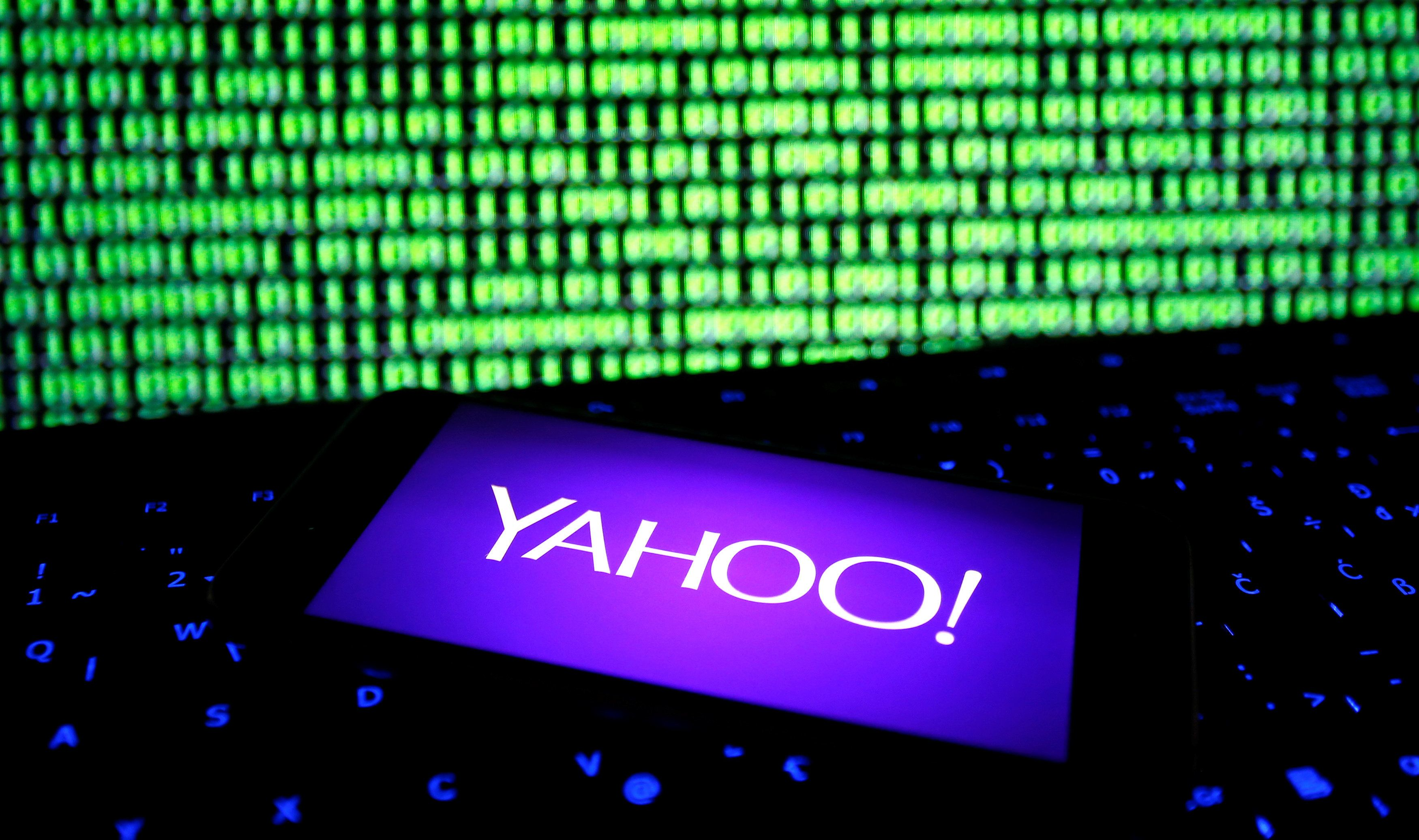 A photo illustration shows a Yahoo logo on a smartphone in front of a displayed cyber code and keyboard on December 15, 2016.