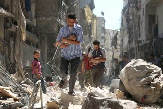 Syrian men carrying babies make their way through the rubble of destroyed buildings following a reported airstrike on the reb