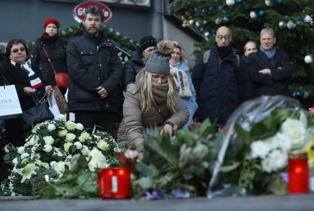 Mourners lay flowers and candles at a makeshift memorial at the site of the