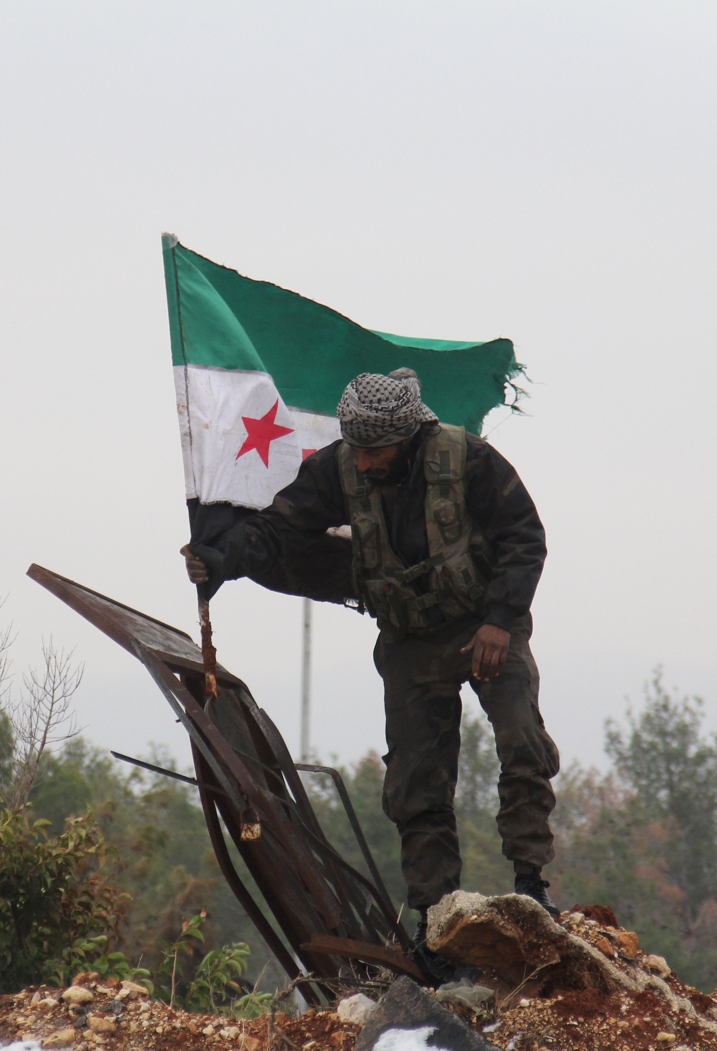 A Syrian rebel fighter places the old Syrian flag, now used by the opposition, in the remains of a damaged sign in a rebel-held territory near Rashidin, west of the embattled city, on December 22, 2016.  Convoys carried opposition fighters out of the last rebel pocket of Aleppo in the final phase of an evacuation clearing the way for Syria's army to retake the city. As part of the Aleppo evacuation deal, it was agreed that some residents would be allowed to leave Fuaa and Kafraya, two Shiite-majority villages in northwestern Syria that are under siege by the Sunni Muslim rebels.     / AFP / Omar haj kadour        (Photo credit should read OMAR HAJ KADOUR/AFP/Getty Images)