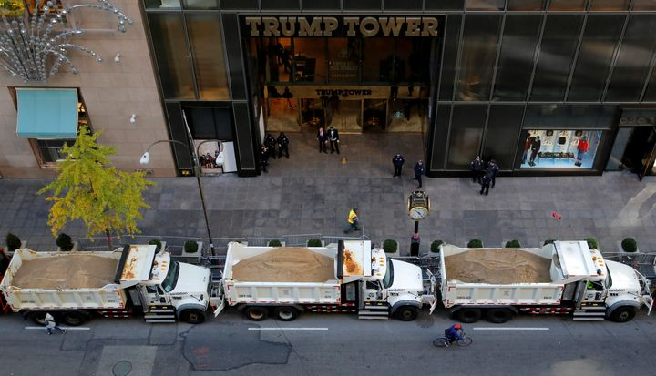 A cyclist rides by a row of sanitation trucks filled with sand acting as barricades along Fifth Avenue outside Republican pre