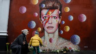 TOPSHOT - Floral tributes are left beneath a mural of British singer David Bowie, painted by Australian street artist James Cochran, aka Jimmy C, following the announcement of Bowie's death, in Brixton, south London, on January 11, 2016. British music icon David Bowie died of cancer at the age of 69, drawing an outpouring of tributes for the innovative star famed for groundbreaking hits like 'Ziggy Stardust' and his theatrical shape-shifting style.   AFP PHOTO / CHRIS RATCLIFFE  RESTRICTED TO EDITORIAL USE, MANDATORY MENTION OF THE ARTIST UPON PUBLICATION, TO ILLUSTRATE THE EVENT AS SPECIFIED IN THE CAPTION / AFP / CHRIS RATCLIFFE        (Photo credit should read CHRIS RATCLIFFE/AFP/Getty Images)