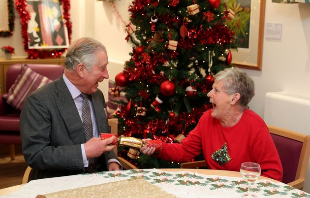 The Prince of Wales pulls a Christmas cracker with Barbara Stacey during a visit to the Sue Ryder Leckhampton...