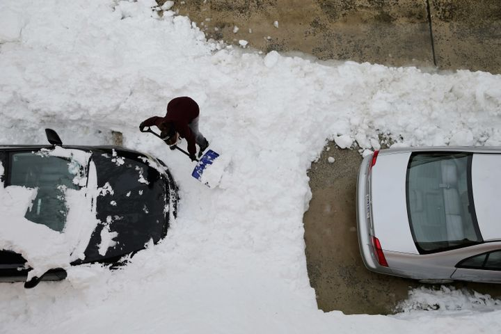 A woman attempts to dig her car out from underneath nearly 20 inches of snow in Washington, D.C., Jan. 26, 2016.