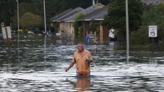 A man wades through a flooded street in Ascension Parish, Louisiana, U.S., August 15, 2016.  REUTERS/Jonathan Bachman/File Photo