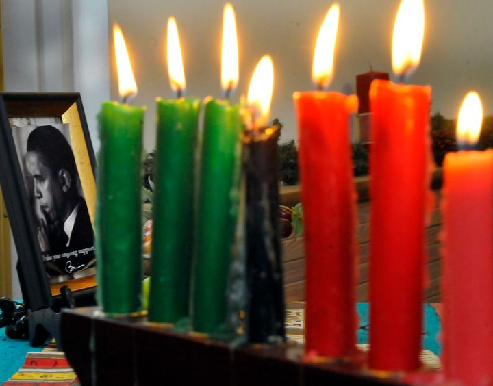 A photograph of President Obama sta beside the lit candles during the Kwanzaa celebration at the Benjamin Banneker Historical
