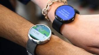 Google employees show off the two different colors of the Moto smartwatch at the Google I/O developers conference in San Francisco June 25, 2014. The round smartwatch will be released in the coming months. REUTERS/Elijah Nouvelage (UNITED STATES - Tags: BUSINESS SCIENCE TECHNOLOGY)