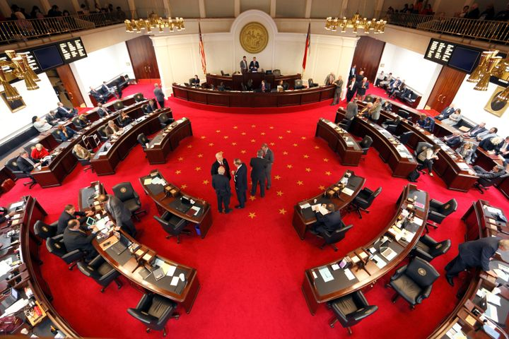 Lawmakers confer during a negotiations on the floor of North Carolina's State Senate chamber as they meet to consider repeali