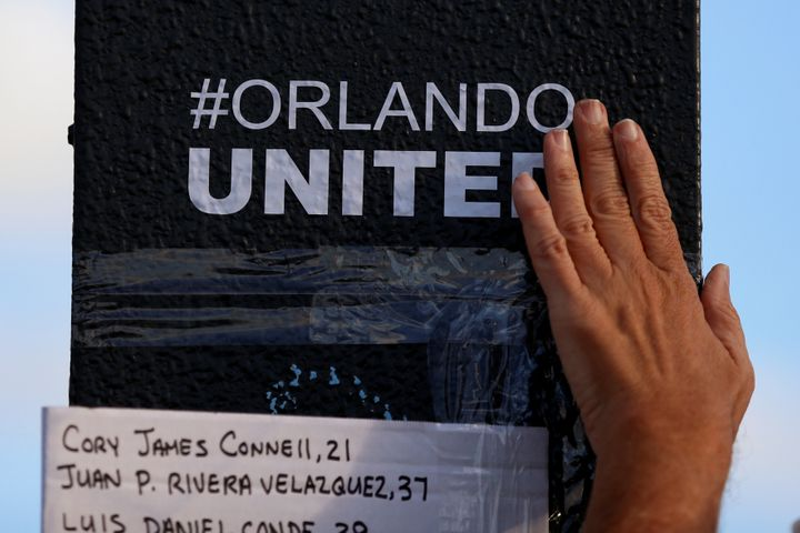 "A person rubs an ""#Orlando United"" sticker on the sign pole outside Pulse nightclub following the mass shooting."