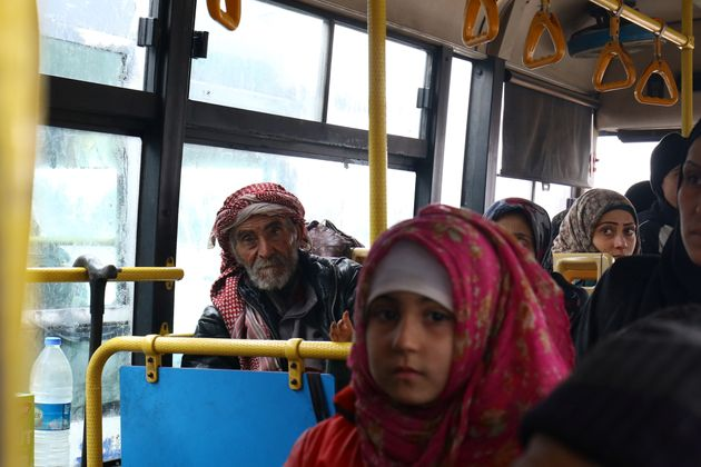 Evacuees from the Shi'ite Muslim villages of al-Foua and Kefraya ride a bus at insurgent-held al-Rashideen...