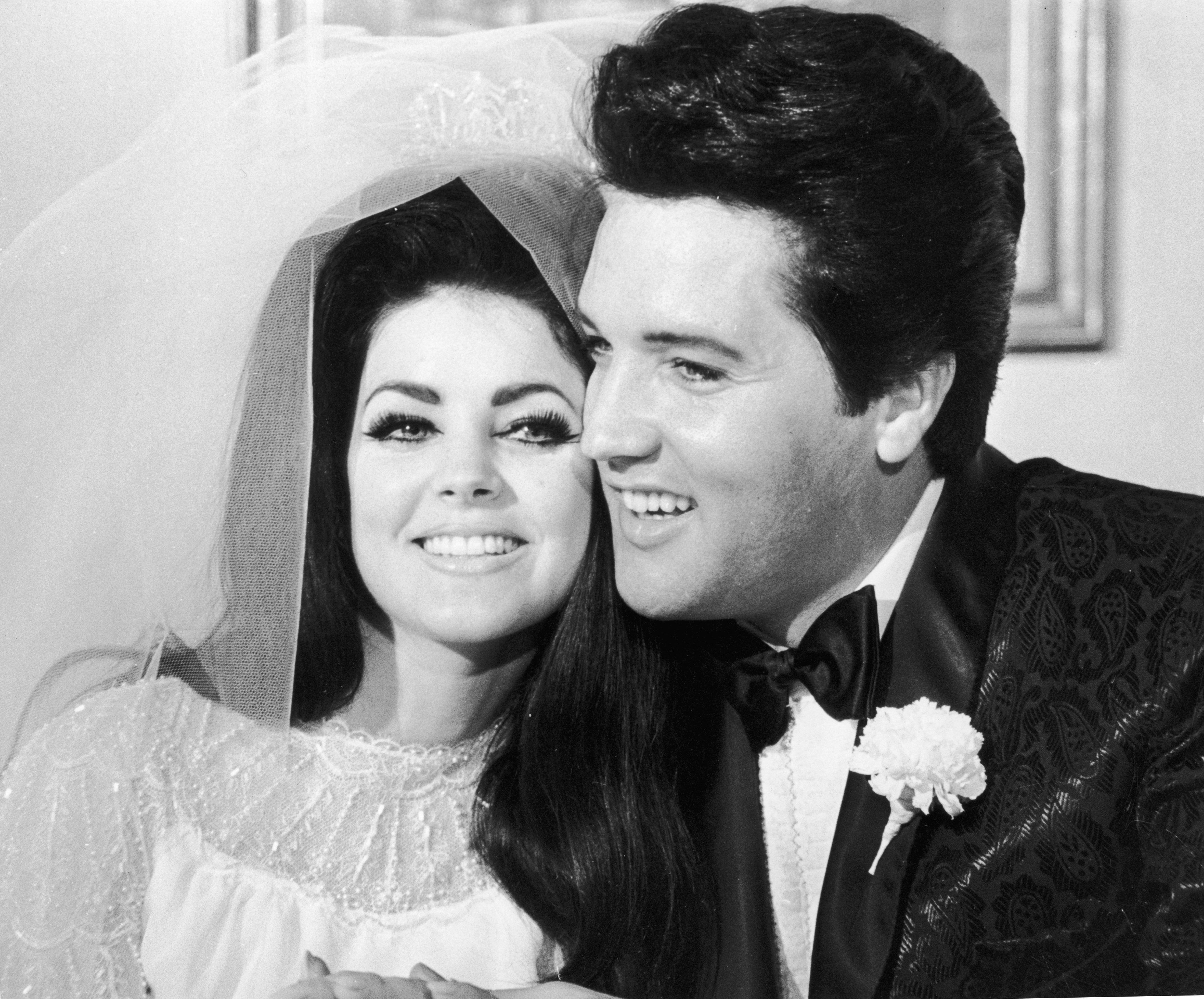 1st May 1967:  American rock musician Elvis Presley (1935 - 1977) and his wife, Priscilla Beaulieu Presley, hugging each other on their wedding day, Las Vegas, Nevada. Priscilla wears her bridal gown and veil, and Elvis wears a shiny paisley jacket.  (Photo by Hulton Archive/Getty Images)