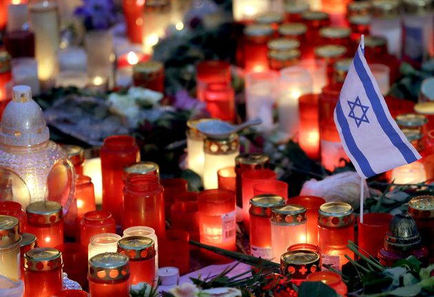 A small flag of Israel is pictured between candles and flowers after the reopening of the Christmas market...
