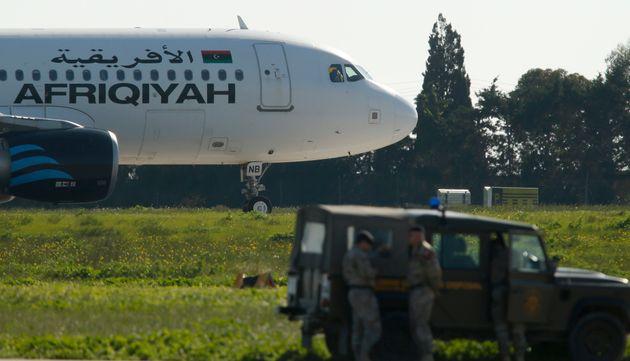 Maltese troops survey a hijacked Libyan Afriqiyah Airways Airbus A320 on the runway at Malta